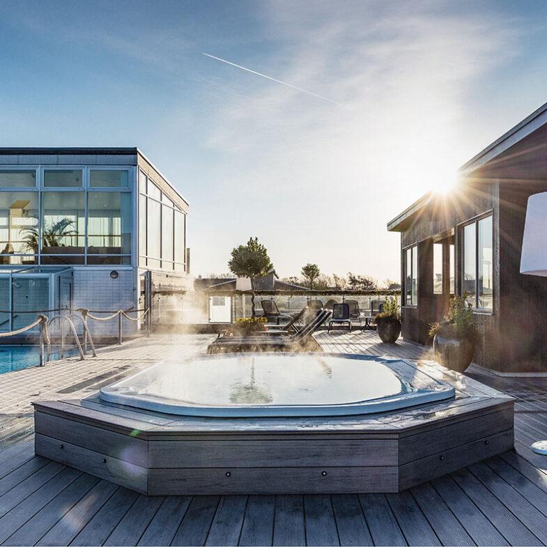 Massagepool i solsken på innergården bredvid bastuhus och pool.