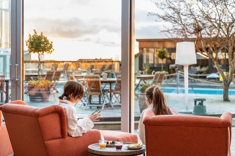 Två kvinnor i fåtöljer i relaxen med utblick över terass, pool och bastuhus.