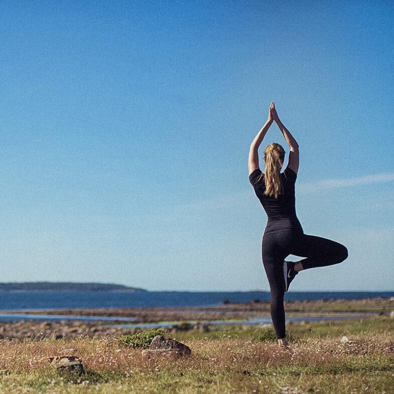 Kvinna utför yoga utomhus med utsikt över havet och hallands väderö