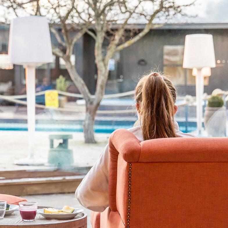 Kvinna i fåtölj och morgonrock i loungen på Torekov Hotell.