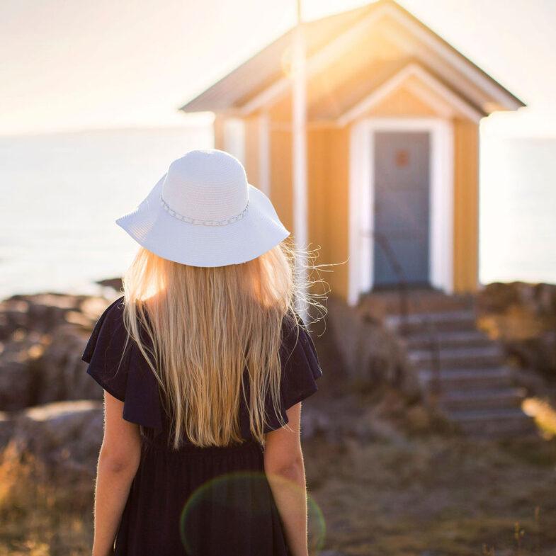 Kvinna med solhatt vid Lotshytten i Torekov. Foto: Louise Nordström Pettersson