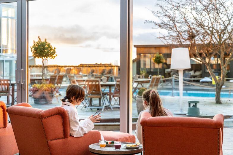 Två kvinnor i fåtöljer i relaxen med vy över terass, bastuhus och pool.